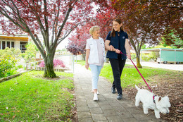 A female resident is strolling in a park assisted by a Home Support Assistant. The Home Support Assistant is also walking a dog on a leash.